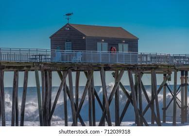 Belmar, NJ USA -- September 9, 2017 - Big waves crash against the wood pilings under the Belmar fishing pier. Editorial Use Only.