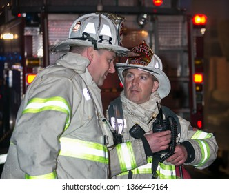 Belmont, MA/ USA - April 18, 2015: Belmont Captain Haley and Watertown Deputy Chief Iannetta discuss operations at the scene of a 3-alarm fire in a commercial taxpayer block Belmont St