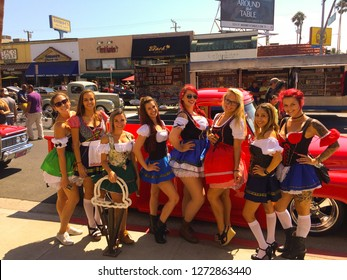 Belmont Shores, California / USA - September 10, 2017: 8 young beautiful women in Oktoberfest dirndl mini dresses standing by a 1955 Ford F100 truck at a classic car show in sunny Southern California