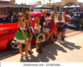 Belmont Shores, California / USA - September 10, 2017: 8 young beautiful women in Oktoberfest dirndl mini dresses posing by a 1955 Ford F100 truck at a classic car show in sunny Southern California