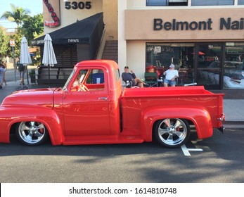 Belmont Shores, California / USA - September 10, 2017: Side view of a red 1955 Ford F100 Pickup Truck as it sits curbside prior to the annual Belmont Shores automobile show