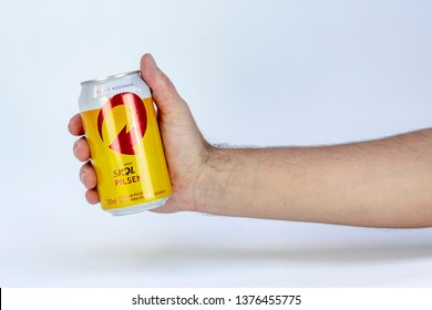 BELO HORIZONTE, BRAZIL - APRIL 19, 2019: Skol pilsen beer can in hand with background isolated on white, Skol is the most popular beer in Brazil, Lager chopp pilsen Brasileira, 350ml,
