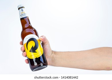BELO HORIZONTE, BRAZIL - JUNE 01, 2019: Skol pilsen beer bottle in hand with background isolated on white, Skol Pure Malt is the most popular beer in Brazil, Lager puro malte Brasileira, 600ml