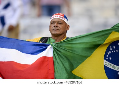BELO HORIZONTE, BRAZIL - June 24, 2014: Fan holding flag of your country during the FIFA 2014 World Cup. Costa Rica is facing England in the Group D at Minerao Stadium