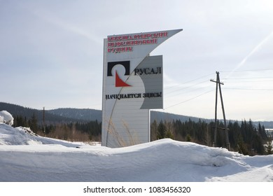 """BELOGORSK, RF - March 18, 2018: Stele with the logo of the company """"RUSAL"""" stands on the road against the background of the taiga.The mine is located in the Kemerovo region.Siberia, Russia."""