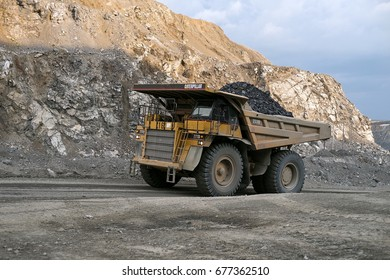BELOGORSK, RUSSIA - JUNE 22, 2014: Dump truck Caterpillar carries ore through a career.The mine is located in the village of Belogorsk, Kemerovo region. Siberia, Russia.