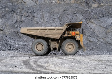 BELOGORSK, RUSSIA - JUNE 22, 2014: Tipper Caterpillar during the work shift in a career, against the background of the rock. Mine is located in the village of Belogorsk, Kemerovo region. Russia
