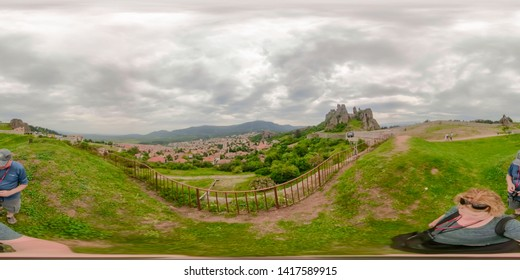 Belogradchik, Bulgaria - May 27, 2019 : Panorama of tourists at Belogradchik Fortress with aerial views of village in rural Bulgaria.