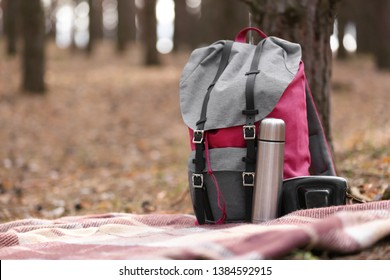 Belongings of tourist on plaid in forest