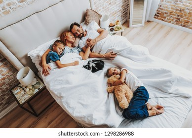 Beloved toys concept. Top view portrait of parents with son and cat sleeping together and little daughter laying lower on bed with teddy bear in hand