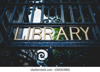 From below of black metal fence with letter Library in it outdoors