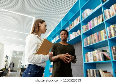 From below Caucasian young woman standing with notebook listening African-American man in library