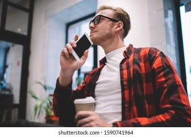 From below concentrated clever peaceful guy dreaming while sitting with coffee and leaning with chin on smartphone in room looking away