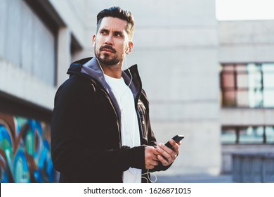 From below of concentrated man in jacket with earphones listening to music browsing smartphone preparing for sport exercise in street looking over shoulder