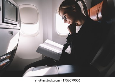 From below crop pensive adult woman in glasses reading book with pleasure while sitting in comfortable armchair and leaning on hand against window in sunbeams in modern airliner