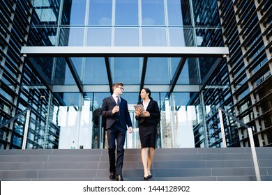 From below of multiethnic woman and man in suits holding coffee cup and tablet walking down steps of office building and talking
