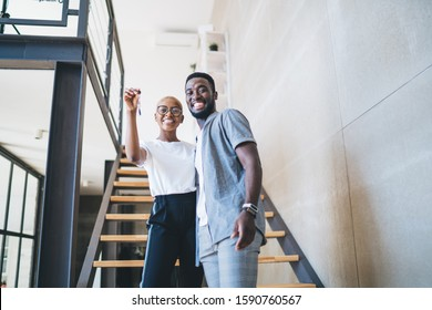 From below pleased black ethnic male and female in modern outfit receiving home key standing on stairs at new home looking at camera