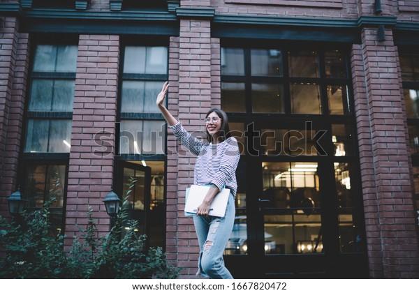 下から見ると、目をそらす建物にノートパソコンを持ち、腕を上げたポジティブなおしゃれな女性の挨拶タクシー