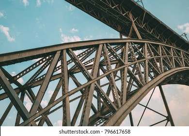 From below shot of metal construction of bridge crossing Douro river in city of Oporto, Portugal.