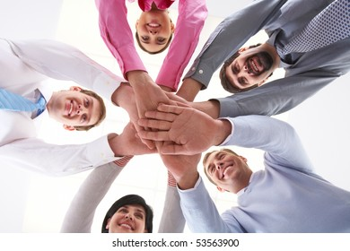 Below shot of smiling co-workers making pile of hands