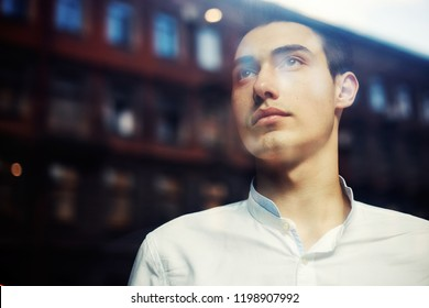 From below shot through window glass of handsome young man in white shirt looking away in contemplation