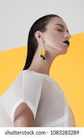 From below shot of young tender model with long wet hair wearing colorful earring and black lipstick with eyes closed.