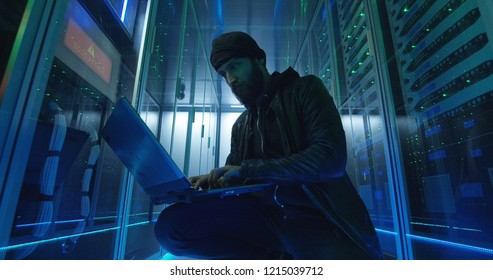 From below side view of bearded man in black using computer and hacking servers of data center launching DDoS attack