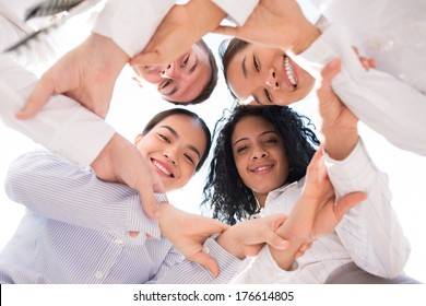 Below view of a business team holding each other'??s hands and smiling at camera