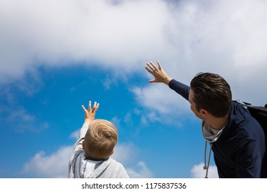 Below view of carefree father and son touching cloudy sky.