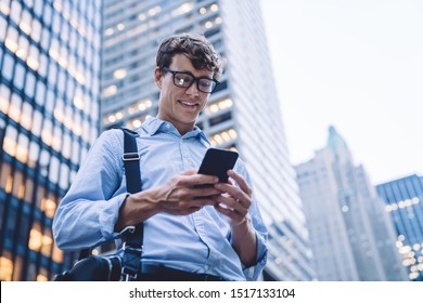 Below view of cheerful corporate employee enjoying online communication in group office chat, successful Caucasian businessman smiling while receiving funny email text on smartphone device