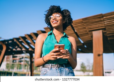 Below view of excited female blogger in stylish eyewear using modern technology and enjoying weather on sunny summer day, happy dark skinned hipster girl holding mobile phone, millennial generation