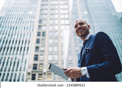 Below view of happy successful entrepreneur dressed in formal wear looking away while installing app on digital tablet using 4G internet walking in modern downtown with high skyscrapers