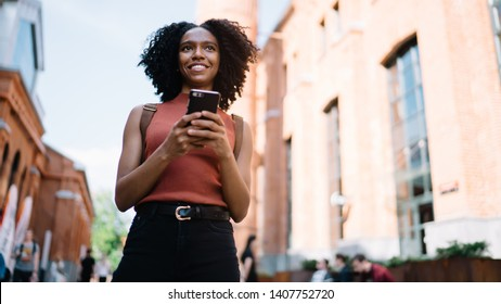 Below view of positive hipster girl looking away and smiling during online communication with followers from social networks, African American female teenager with modern technology in hand