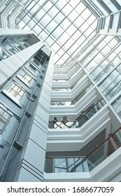Below view of several business people discussing working points while standing on one of balconies inside large office center