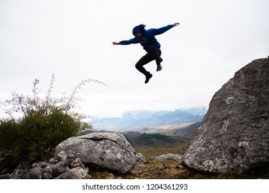 From below view of sportive man jumping from rock to rock doing parkour in afternoon on mountain.