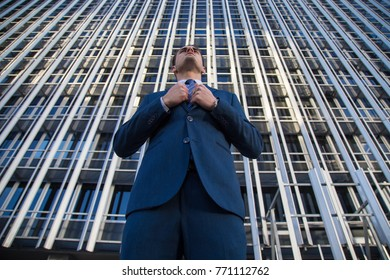 From below view of stylish man in elegant suit posing confidently on background of modern office skyscraper.