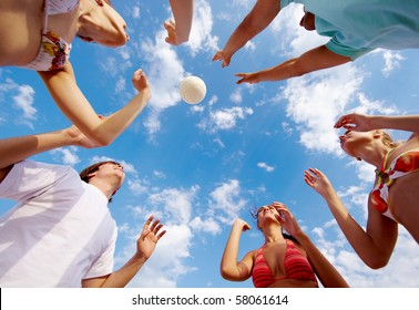 Below view of teenage friends catching ball on background of cloudy sky