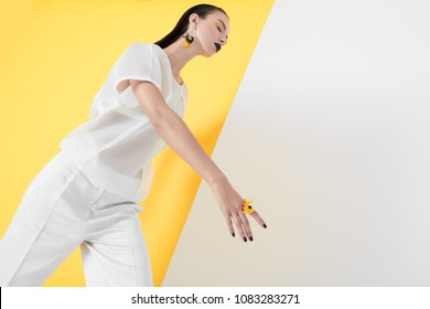 From below of vogue model in white and bright accessories walking with eyes closed on colorful background.