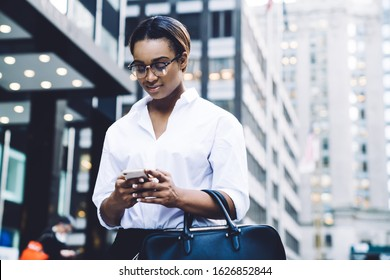From below of young African American businesswoman in eyeglasses wearing white blouse holding black handbag and texting message on smartphone while standing next to office buildings