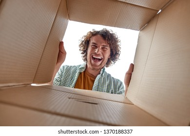 From below young guy with curly hair looking inside open carton box with excited face expression while moving into new place
