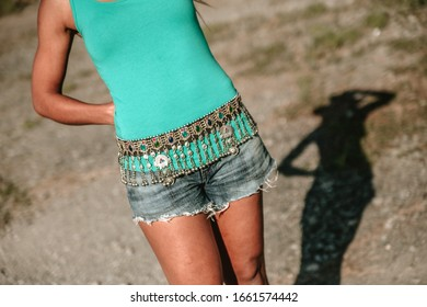 Belt over woman's body with green shirt and its shadow cast on the floor