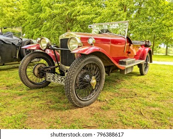Belton, Leicester - 6th June 2015: Red convertable Frazer-Nash sports car parked on grass under a tree.