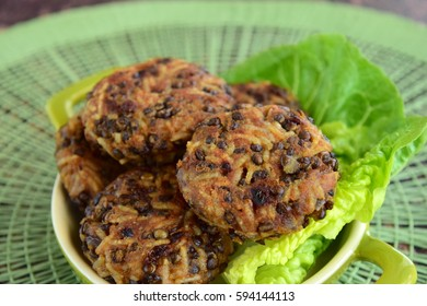 Beluga lentil rice patties on lettuce salad