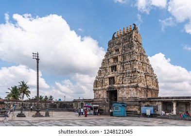 Belur, Karnataka, India - November 2, 2013: Brown stone Gopuram of main entrance seen from inside temple against blue sky. Booths, signs and people. Ceremonial flag pole against white cloud.