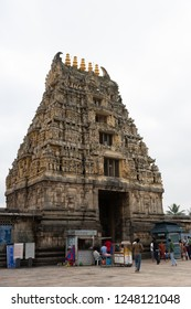 Belur, Karnataka, India - November 2, 2013: Brown stone Gopuram of main entrance seen from inside temple against silver sky. Booths, signs and people.