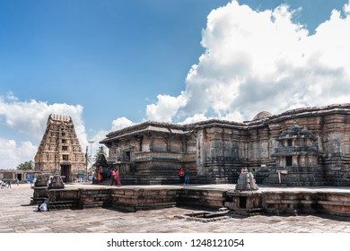 Belur, Karnataka, India - November 2, 2013: Chennakeshava Temple. Brown stone Gopuram of main entrance in back with Kesava sanctuary up front under blue sky with white clouds. People add color.