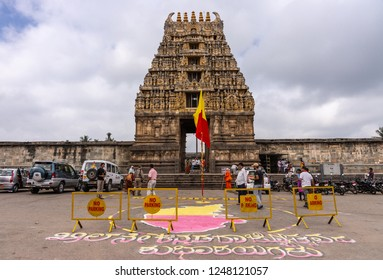 Belur, Karnataka, India - November 2, 2013: Brown stone Gopuram of main entrance seen from street against white cloudy sky. Karnataka Rajyotsava sign and flag up front. People and cars.
