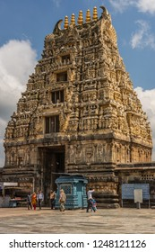 Belur, Karnataka, India - November 2, 2013: Brown stone Gopuram of main entrance seen from inside temple against blue sky. Booths, signs and people.