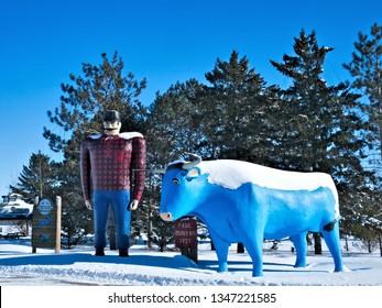 BEMIDJI, MN - 8 FEB 2019: Statue of Paul Bunyan and Babe the Blue Ox, Legendary Lumberjack - popular roadside landmark - Bemidji MN on a sunny winter day.