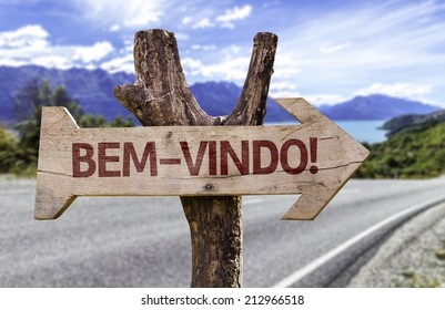 """""""Bem-Vindo!"""" (In Portuguese: Welcome) wooden sign with a road background"""